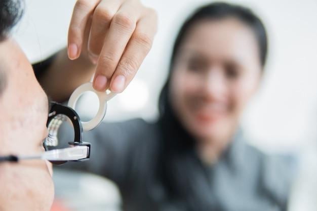 Une ophtalmologiste sur un cadre d'essai lorsqu'elle est avec le patient à la clinique