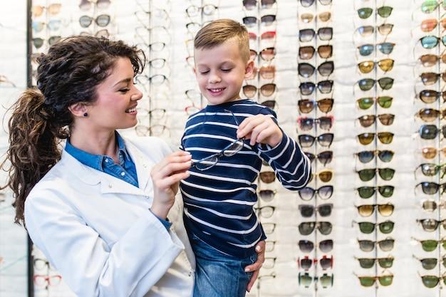 Ophtalmologiste choisissant un cadre oculaire pour un petit garçon dans un magasin d'optique.