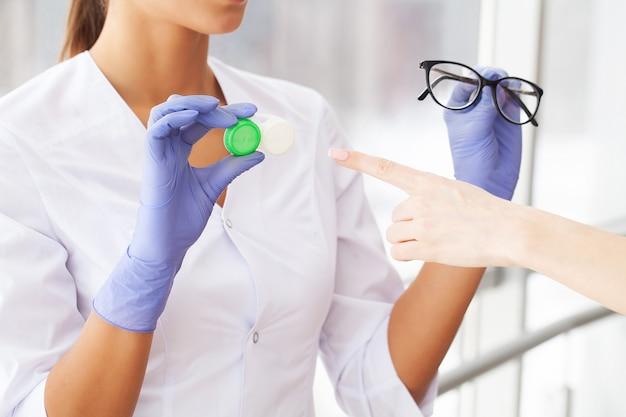 Ophtalmologiste choisissant entre des lunettes et des lentilles devant le tableau des yeux dans l'armoire