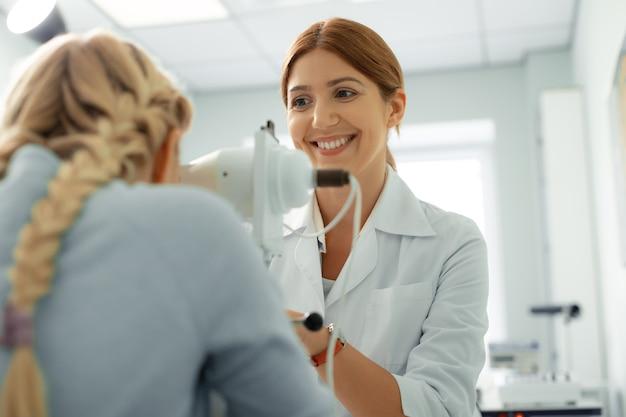 Ophtalmologiste joyeux. ophtalmologiste roux gai souriant tout en s'asseyant devant la fille
