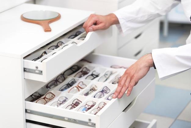 Ophtalmologiste mains se bouchent, choisissant des lunettes dans un tiroir du magasin d'optique