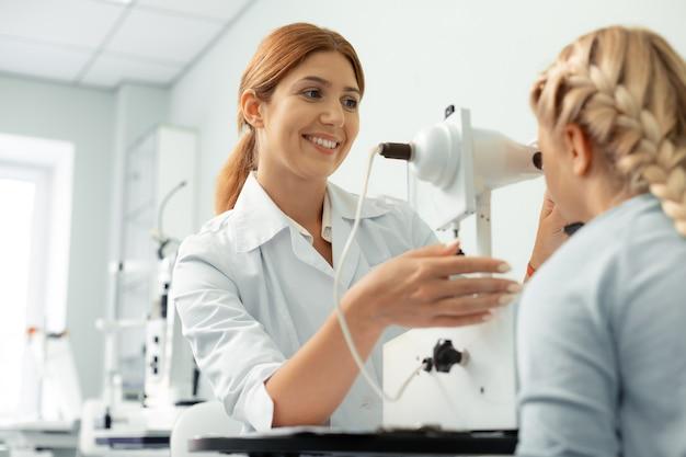 Ophtalmologiste se sentant joyeux. belle ophtalmologiste aux cheveux roux se sentant joyeuse lors de l'examen d'une fille