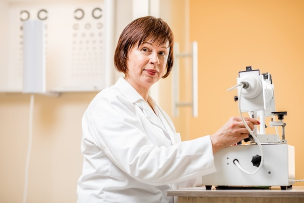 Ophtalmologiste senior travaillant avec du matériel de vision au bureau
