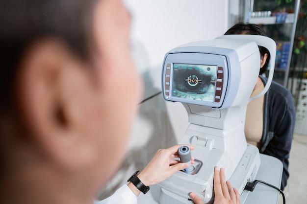 Un ophtalmologiste utilise un ordinateur oculaire pour qu'une patiente examine les yeux du patient dans une clinique ophtalmologique