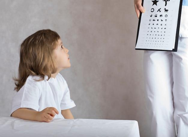 L'ophtalmologiste vérifie la vision d'un garçon de 5 ans au moyen d'un tableau des yeux pour les enfants.