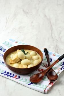 Opor tahu telur puyuh ou curry indonésien avec tofu et œuf de caille, servi sur un bol brun avec espace de copie pour le texte ou la recette.