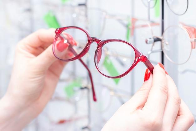 Opticien dans le magasin détient des lunettes.