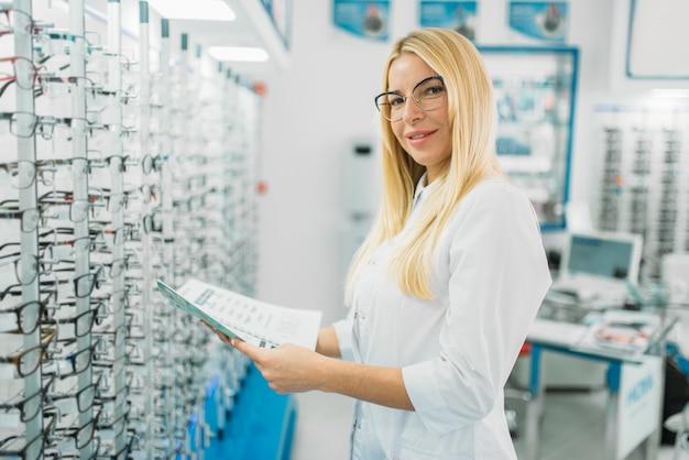 Opticien féminin avec catalogue de lunettes en mains