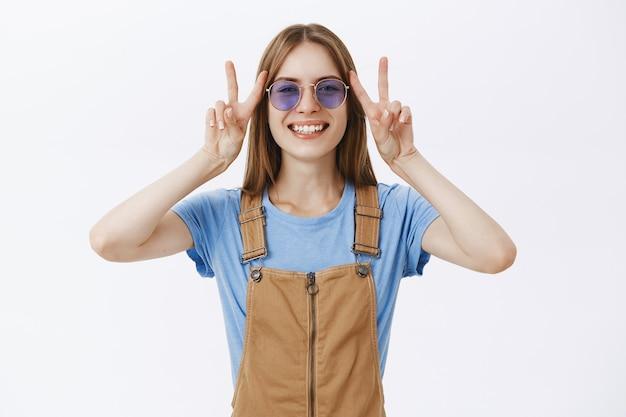 Optimiste heureuse jolie fille montrant le geste de paix et souriant insouciant