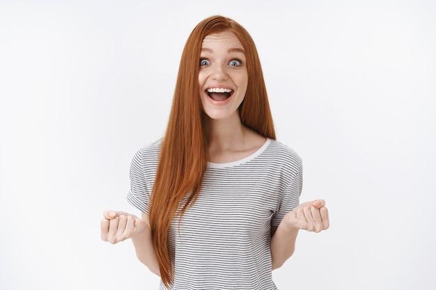 Optimiste heureux excité rousse mignonne adolescente yeux bleus souriant ravi recevoir une opportunité géniale chance bonne nouvelle debout triomphant surpris, mur blanc serrer les poings joyeusement