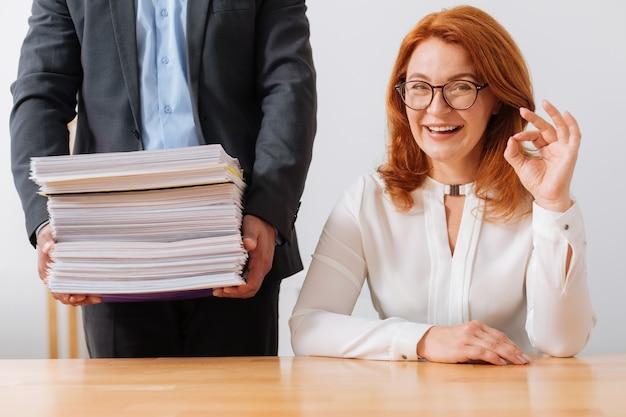 Optimiste, joyeuse femme brillante assise sur son lieu de travail et recevant une pile de documents dont elle a besoin aujourd'hui