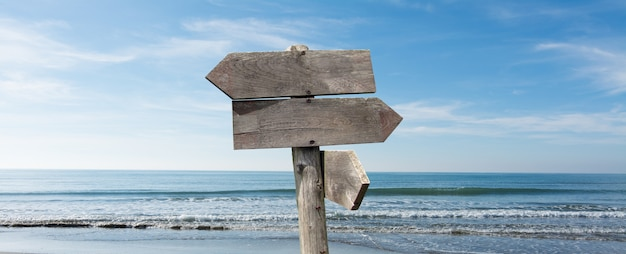 Options de destinations de voyages d'été. panneau de signalisation de direction avec des flèches en bois sur la plage et la mer