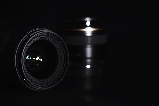 Optique à la caméra sur le bureau de l'opérateur. éclat dans le verre d'un objectif photo. fond noir avec la technique du photographe.