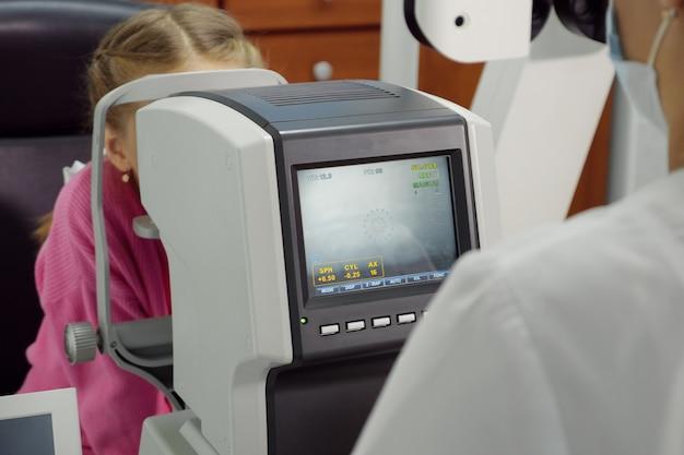 L'optométriste examine la vue de la petite fille.