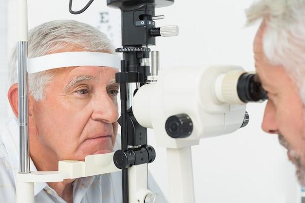 Optométriste faisant des tests de vue pour un patient senior