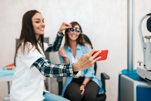 Optométriste féminine prenant une photo de selfie après un examen de la vue.