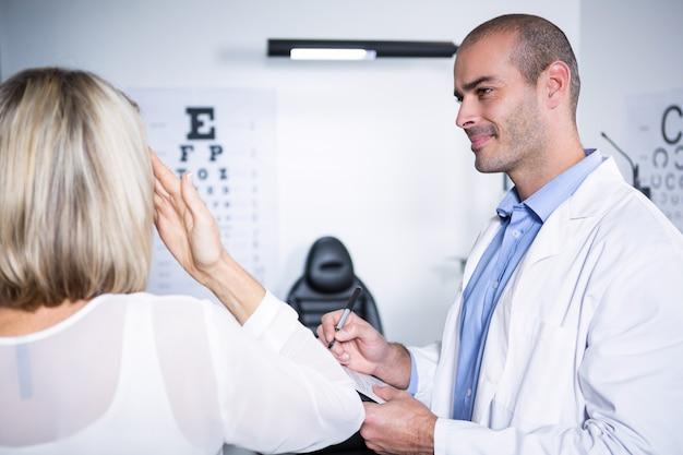 Optométriste mâle prenant le test de la vue d'une patiente