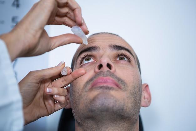 Optométriste mettant des gouttes dans les yeux des patients