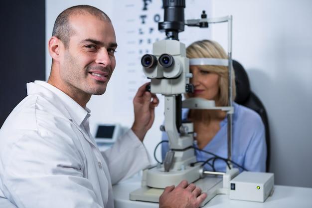 Optométriste souriant examinant une patiente sur une lampe à fente