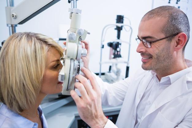 Optométriste souriant examinant une patiente sur un réfracteur
