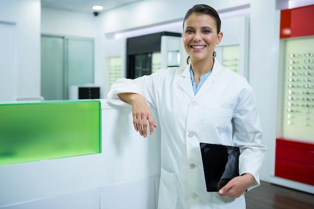 Optométriste tenant une tablette numérique dans un magasin d'optique