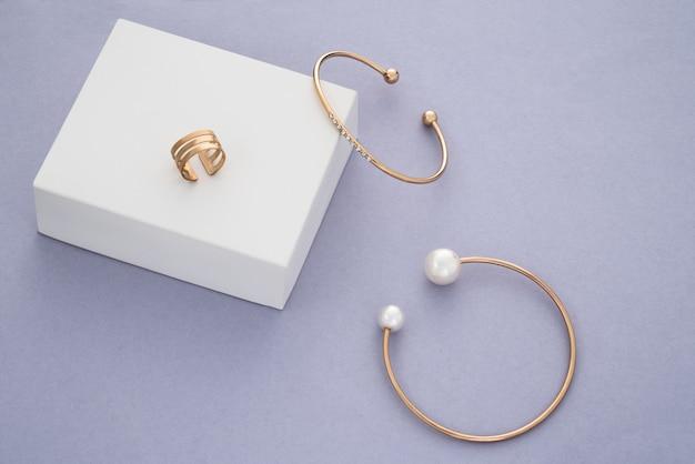 Or avec des bracelets modernes de pierres précieuses et une bague sur une boîte blanche sur fond violet