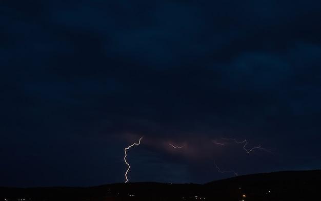 Orage dans le ciel nuageux sombre illuminé par l'éclat de la foudre, phénomène naturel