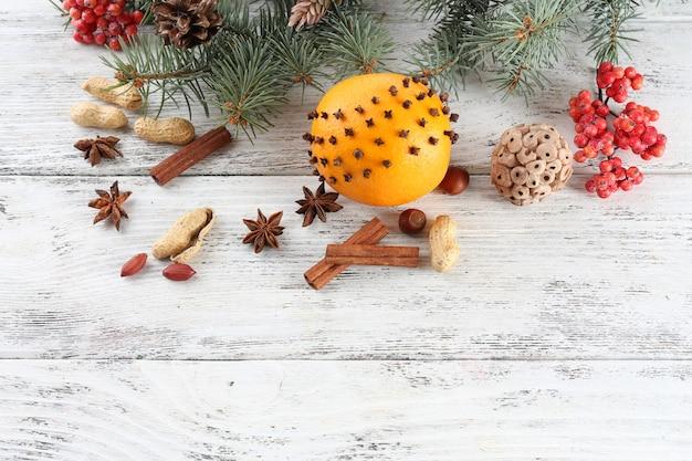 Orange aux épices, sorbier des oiseleurs et brin de pin de noël sur fond de bois de couleur