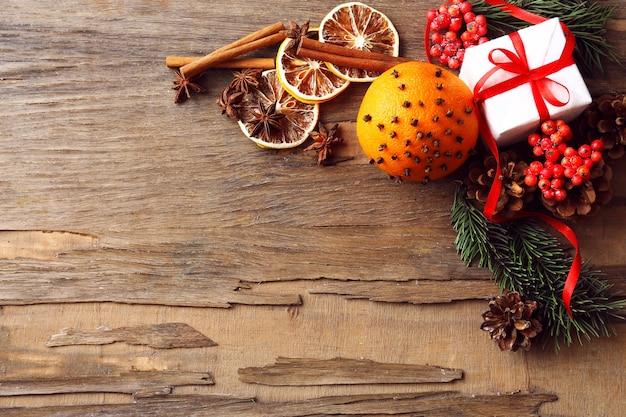 Orange avec boîte présente, épices, tranches de citron séché et brins d'arbre de noël sur fond de bois rustique