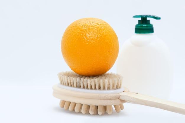 Orange sur brosse de massage manuelle double face et crème pour le corps avec distributeur sur fond blanc