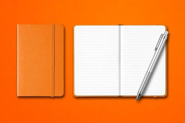 Orange cahiers fermés et ouverts avec un stylo isolé sur coloré