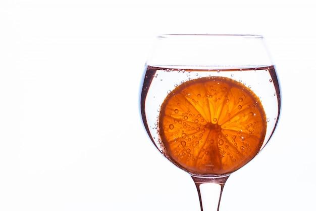 Orange dans de l'eau minérale isolée sur fond blanc