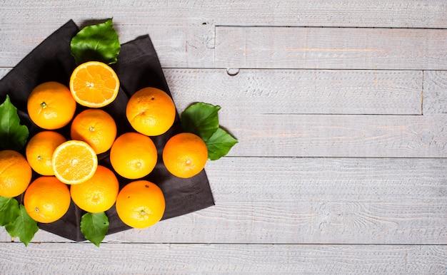 Orange douce avec des feuilles sur fond en bois. vue de dessus,