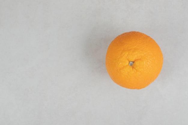 Orange entière fraîche sur une surface grise