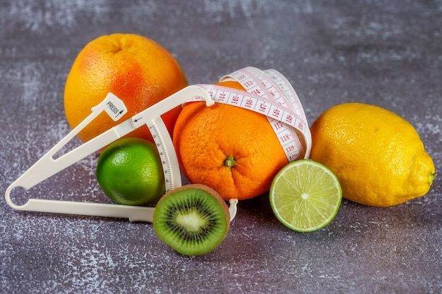 Une orange enveloppée d'un ruban à mesurer et d'un pied à coulisse entouré de fruits frais sur un fond de béton gris. le concept de minceur, éliminer la cellulite, mettre la silhouette en forme.