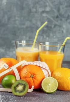 Une orange enveloppée d'un ruban à mesurer et d'un pied à coulisse entouré de fruits frais et de verres de jus et de smoothies sur un fond de béton gris. le concept de minceur, met la silhouette en forme.