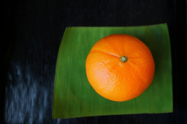 Orange sur la feuille de bananier verte avec sur la table en bois. concept alimentaire.