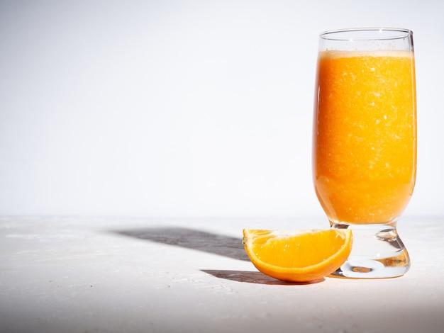 Orange fraîche dans une tasse en verre sur fond blanc avec des ombres. copyspace.