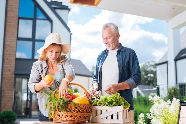 Orange fraîche. femme au foyer attrayante tenant une belle orange fraîche après avoir acheté de la nourriture avec son mari tout en se tenant près de son mari