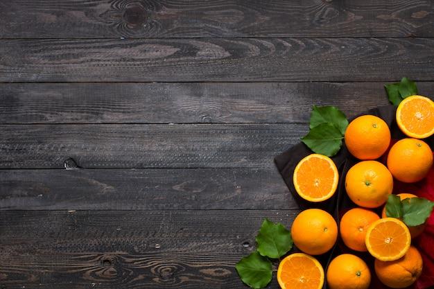 Orange fraîche avec des feuilles sur bois