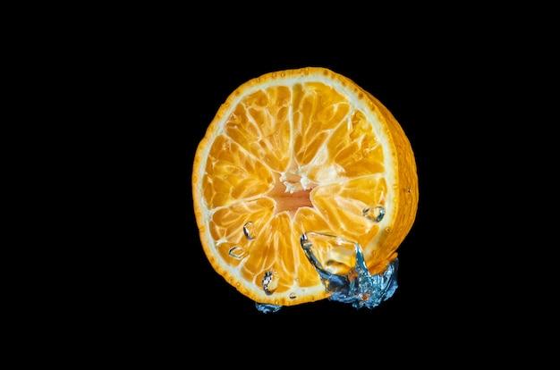 Orange fraîche tombant dans l'eau avec des éclaboussures sur fond noir
