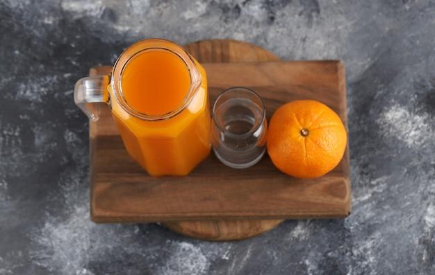 Orange, jus et verre vide sur planche de bois.