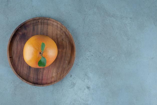 Orange juteuse mûre sur une plaque en bois, sur le fond de marbre. photo de haute qualité