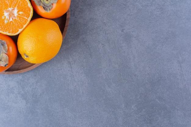 Orange et kaki sur plaque de bois sur table en marbre.