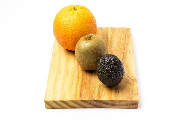 Orange, kiwi et avocat sur une planche de bois