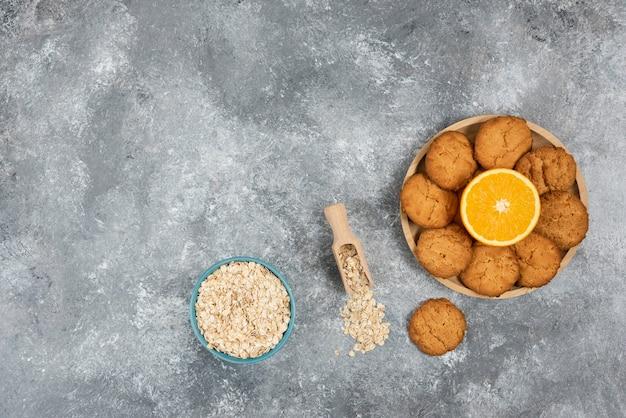 Orange à moitié coupée avec des biscuits faits maison sur une planche de bois et des flocons d'avoine dans un bol sur une table grise.