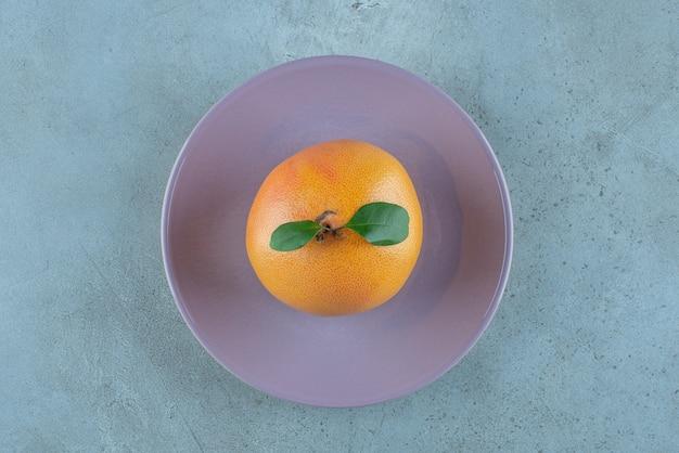 Orange mûre fraîche sur une assiette, sur le fond de marbre. photo de haute qualité