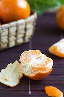 Orange pelée fraîche par un peu d'orange dans un panier