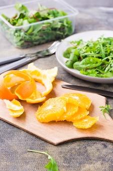 Orange pelée et tranchée sur une planche à découper et un mélange de roquette, de bette à carde et de mizun sur une assiette sur la table.