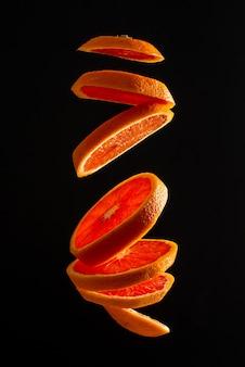 Une orange rouge tranchée lévite dans l'air. photo créative d'orange volant sur fond noir
